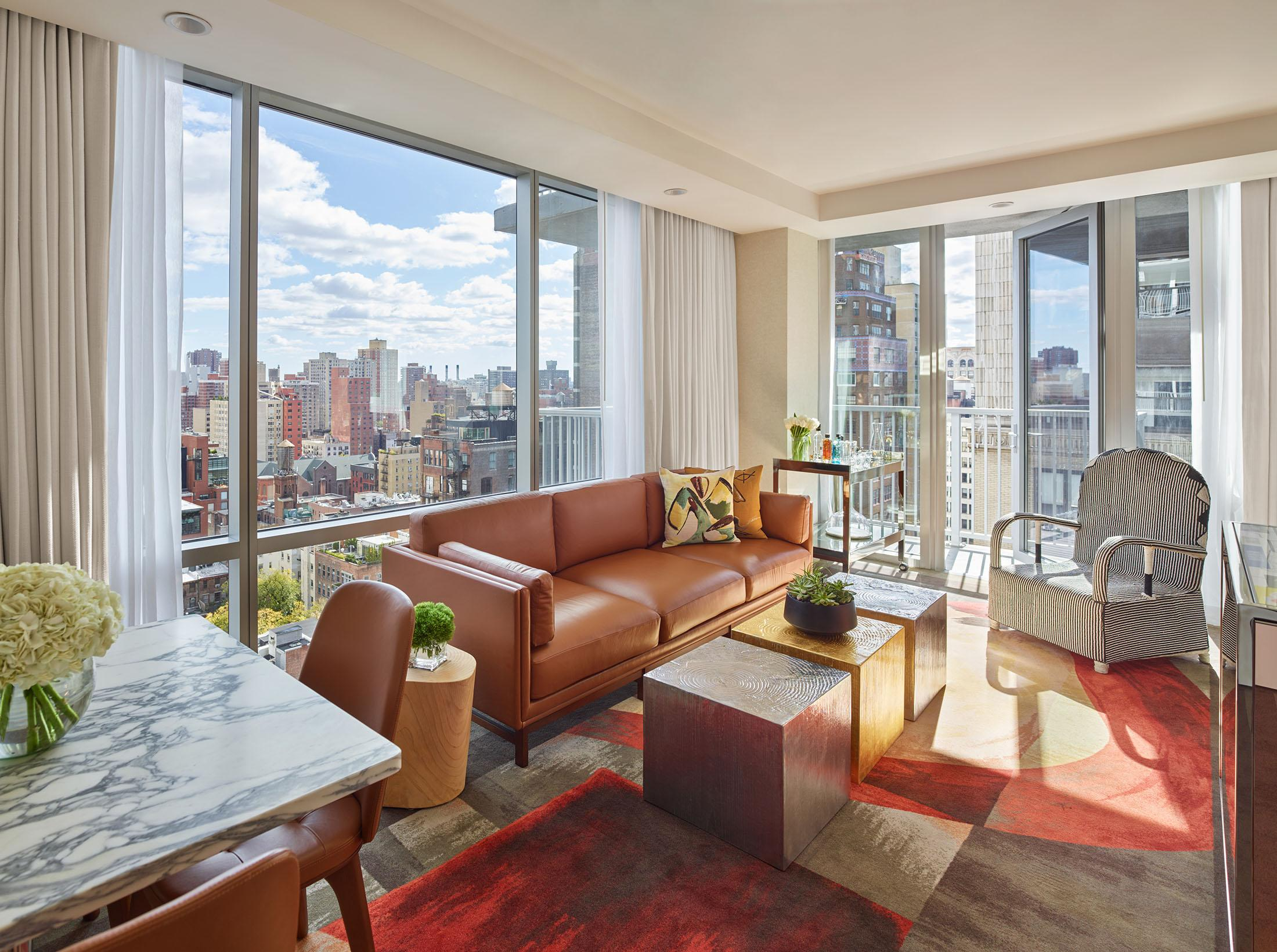 A bright hotel room suite with floor to ceiling windows